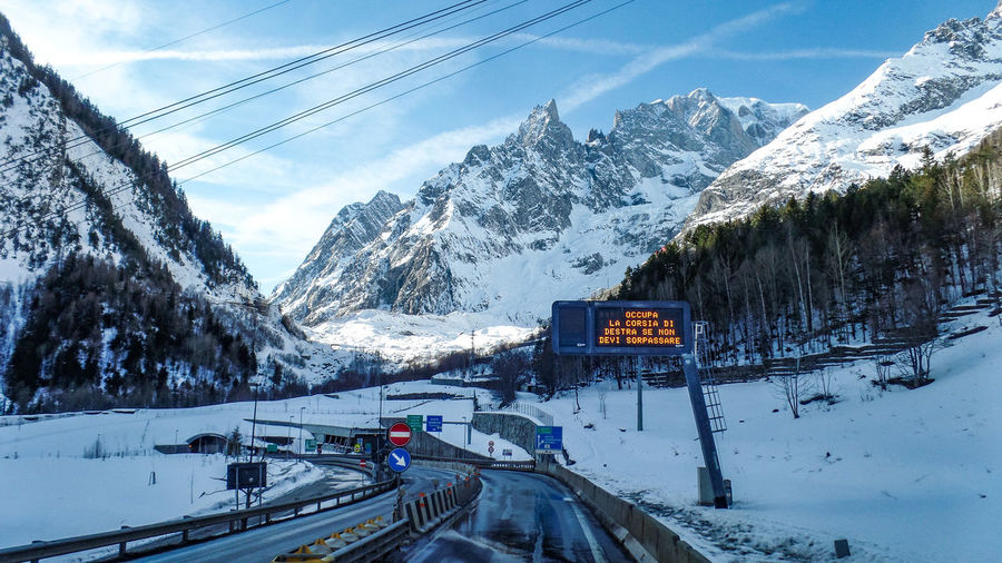 Winter Snow Cold Temperature Mountain Transportation Sign Mode Of Transportation Mountain Range Sky Scenics - Nature Beauty In Nature Nature Cloud - Sky Cable Snowcapped Mountain Road No People Information Communication Electricity  Outdoors