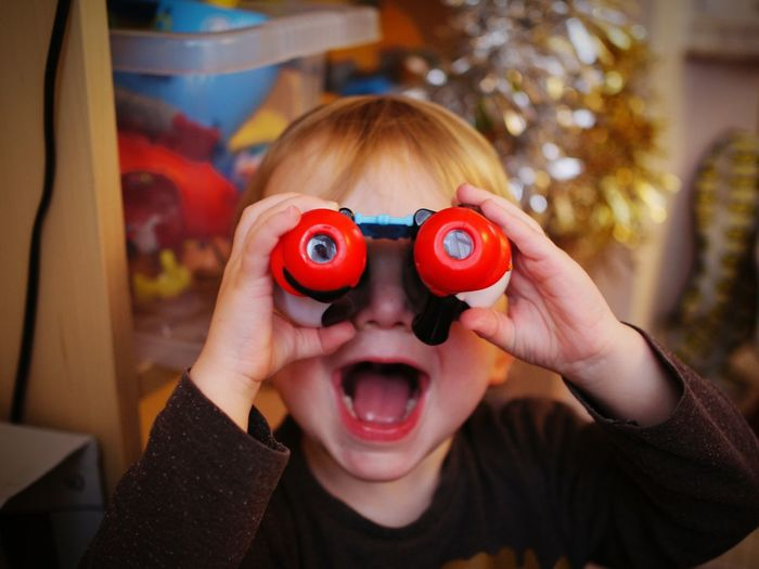 Close Up Of Boy Looking Through Binoculars At Home