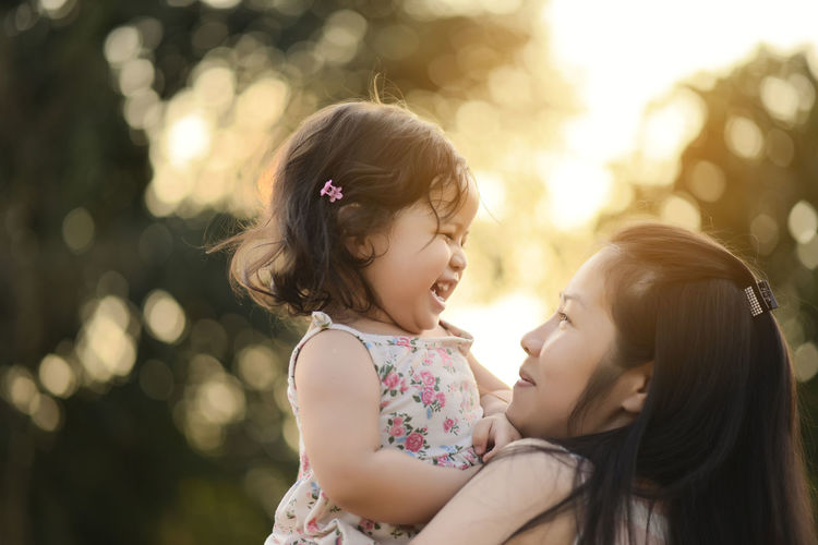 Sweet Beautiful baby girl with hug of mother and playing. Happy loving family kissing and hugging. Bonding Childhood Close-up Cute Daughter Day Family Family With One Child Focus On Foreground Girls Happiness Leisure Activity Lifestyles Love Mother Nature Outdoors People Real People Side View Smiling Togetherness Tree Young Adult Young Women