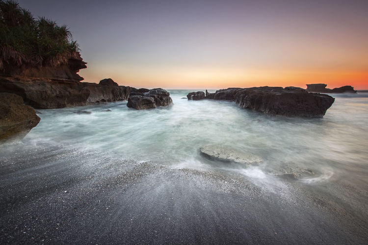 A view of wave motion on the sand with rocks formation taken with slow shutter. Soft focus blur due to Slow Shutter speed. Asian  Bali Natural Wave Ambient Beauty In Nature Clear Sky Day Horizon Over Water Motion Nature No People Outdoors Peaceful Rock - Object Scenics Sea Sky Slow Shutter Smooth Sunset Tranquil Scene Tranquility Water Wave