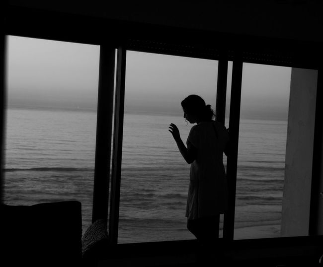 Woman standing at window against sea