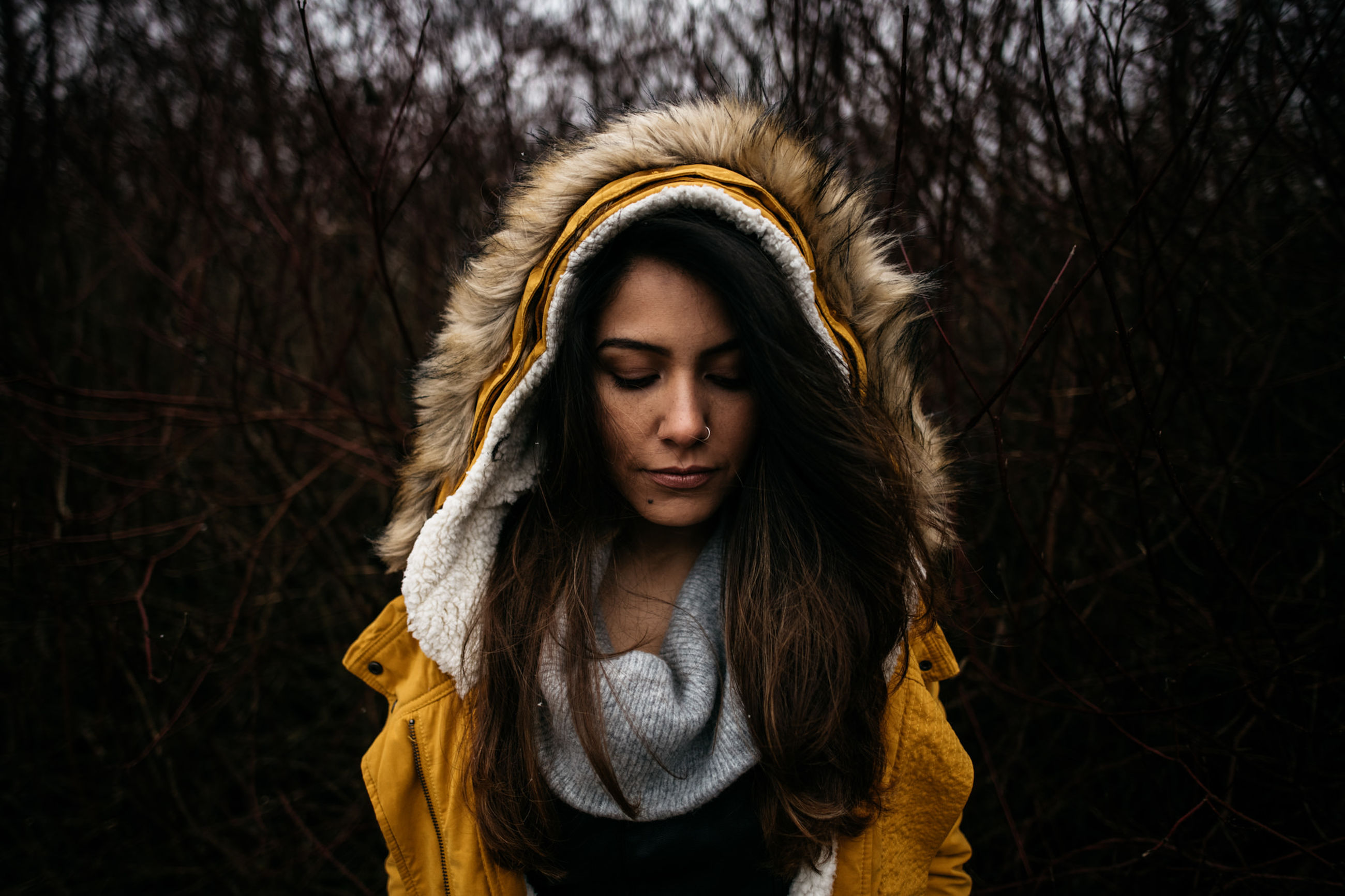 front view, one person, clothing, real people, young women, lifestyles, portrait, young adult, tree, warm clothing, winter, jacket, headshot, standing, leisure activity, hair, fur, looking down, contemplation, hood - clothing, outdoors, hairstyle, scarf, beautiful woman