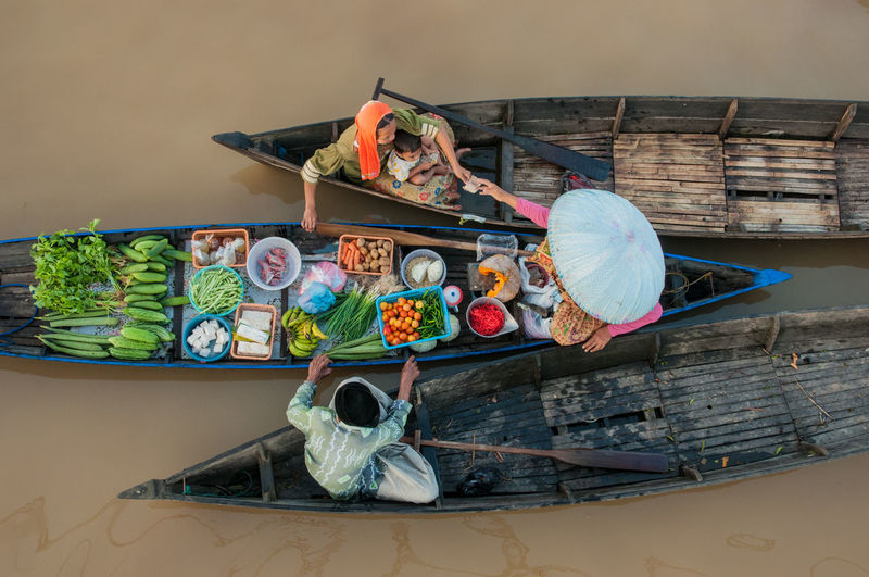 High angle view of woman buying vegetable at floating market