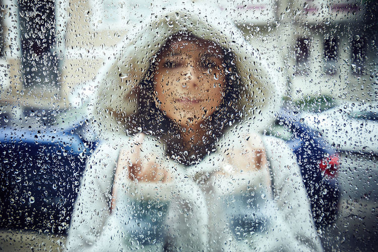 Portrait of woman seen through wet window in rainy season