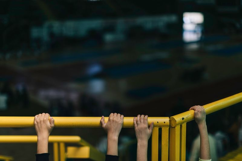 Cropped hands of children holding railing