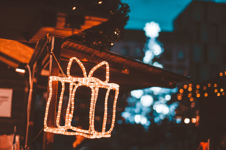 Low angle view of illuminated christmas lights hanging at night
