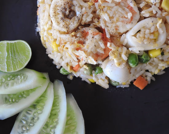 Fried rice and seafood with corns,carrots and beans decor by cucumbers and lemon sliced Close-up Cucumber Day Food Food And Drink Freshness Healthy Eating Indoors  Lime No People Ready-to-eat SLICE