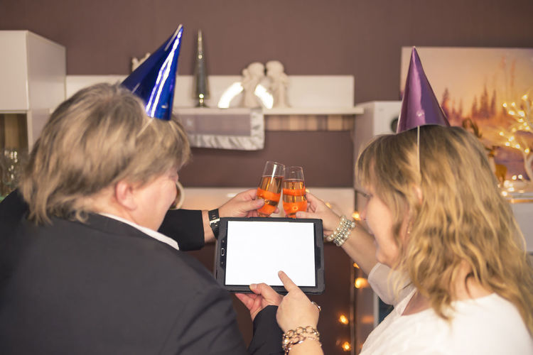 Couple watching during New Year's Eve party at a Tablet PC Champagne Copy Space Couple Home New Year's Eve Read Alcohol Celebration Communication Festive Clothes Flat Greetings Happy New Year Hats Live View Lives Cheers Man Party Party Cap Point The Finger Real People Social Media Tablet Pc Wireless Technology Women