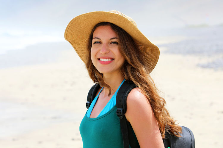Portrait of smiling young woman standing at beach