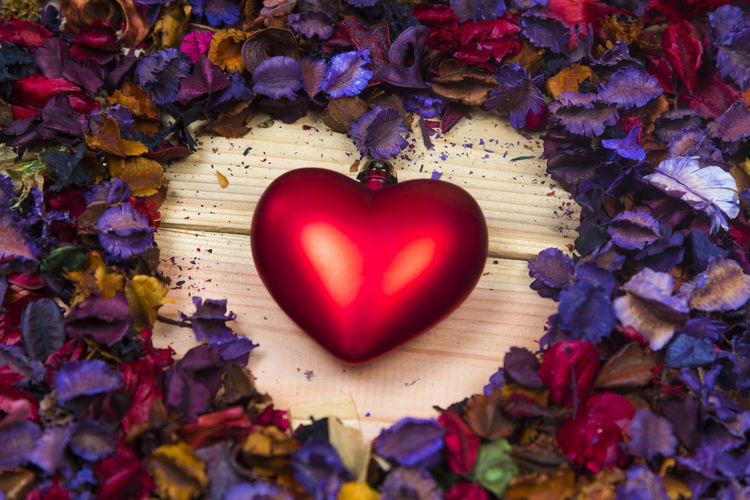 Close-Up Of Heart Shape Amidst Petals On Table