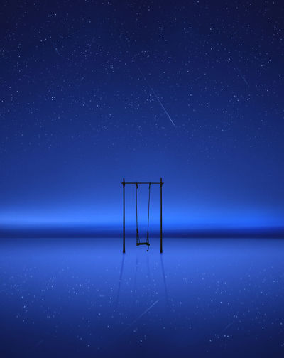 Swing over sea against clear blue sky at night