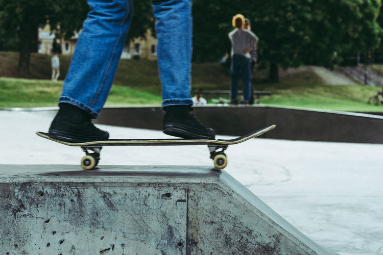 Low Section Of Boy Standing On Skateboard
