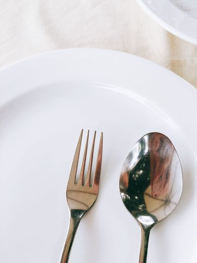 Close-Up Of Fork By Spoon In Plate On Table