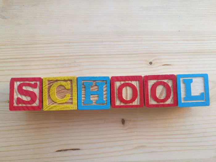 School text made from multi colored letter blocks on table