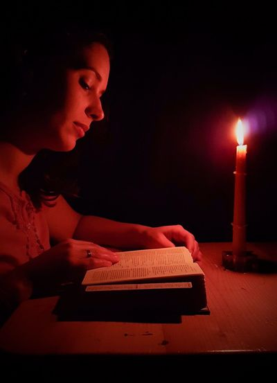 Side View Of Woman Reading Book By Burning Candle On Table In Dark
