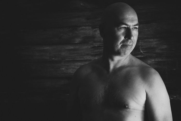 Shirtless man standing in darkroom