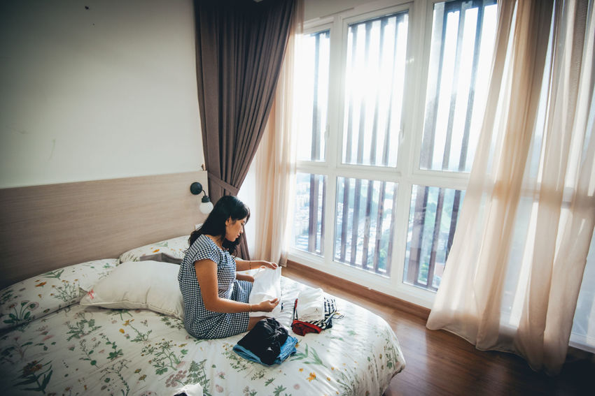 One Person Sitting Curtain Furniture Real People Indoors  Full Length Window Lifestyles Bed Day Leisure Activity Casual Clothing Young Adult Domestic Room Relaxation Home Interior Young Women Side View Wireless Technology Hairstyle Using Laptop