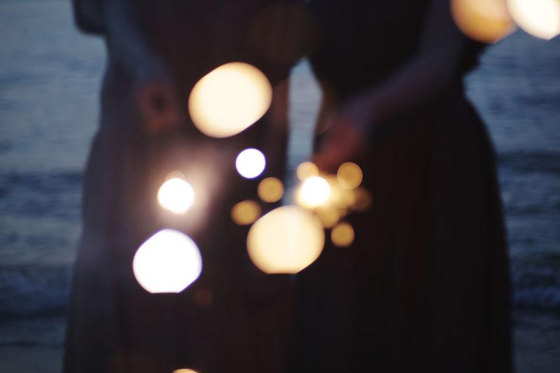 Close-up of hand holding illuminated lights over sea