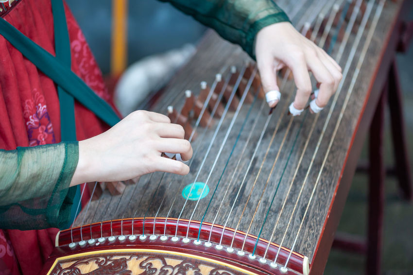 playing guzheng Arts Culture And Entertainment Day Finger Focus On Foreground Guzheng Hand Human Body Part Human Hand Indoors  Midsection Music Musical Equipment Musical Instrument Musician One Person Performance Playing Plucking An Instrument Real People Skill  String Instrument