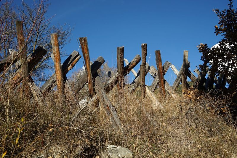 Fence on landscape against clear sky