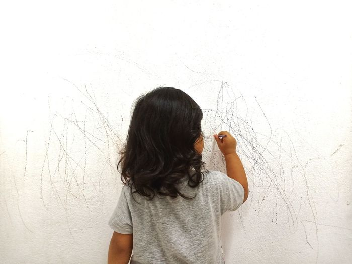 Picture from a back of a little girl drawing creatively on a white wall
