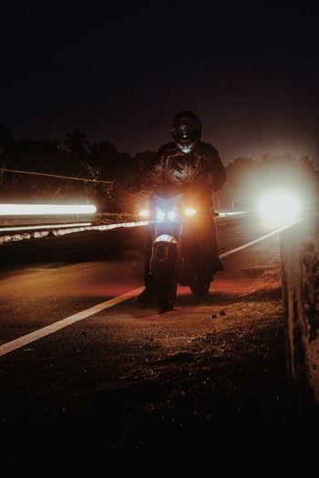 Man riding motorcycle on road at night