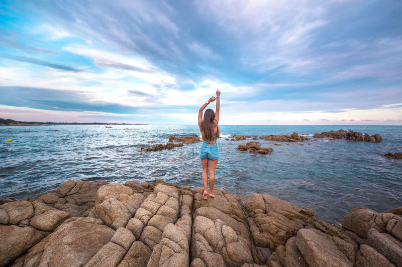 Rear view of person standing on rock by sea against sky