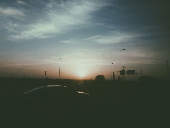 Silhouette cars on road at sunset