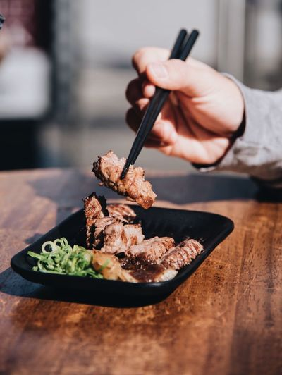 Cropped Hand Having Meat On Wooden Table