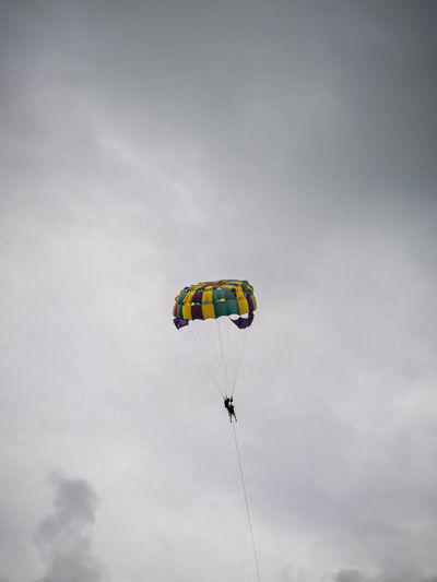 Low angle view of person parasailing against sky