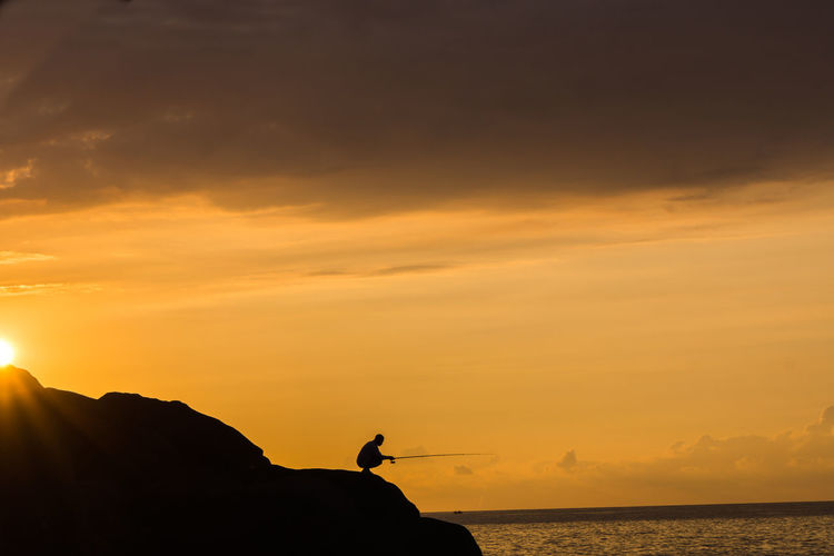 Silhouette Person Fishing At Beach Against Sky During Sunset