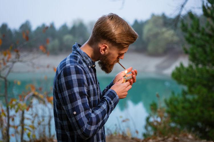 Smoking bearded man outdoors near lake in the evening. bad habit, addiction