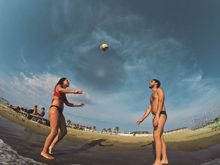 Young couple playing with ball at beach against sky