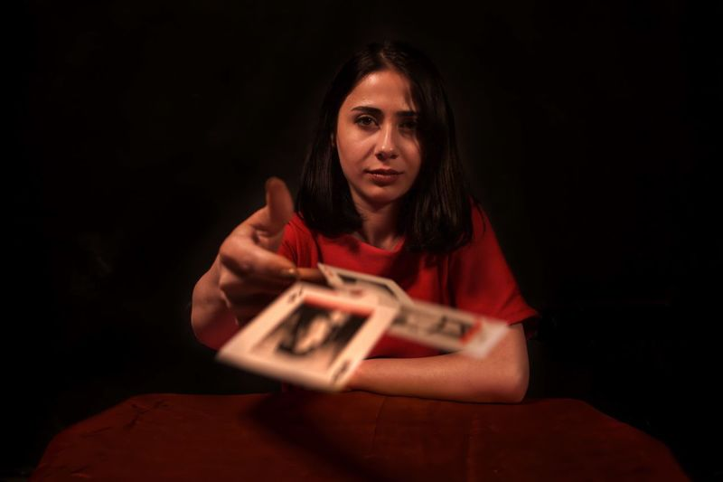 Portrait Of Woman Holding Playing Cards Against Black Background