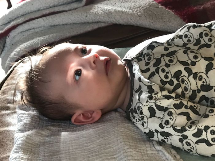 High angle view of cute baby girl lying on bed at home