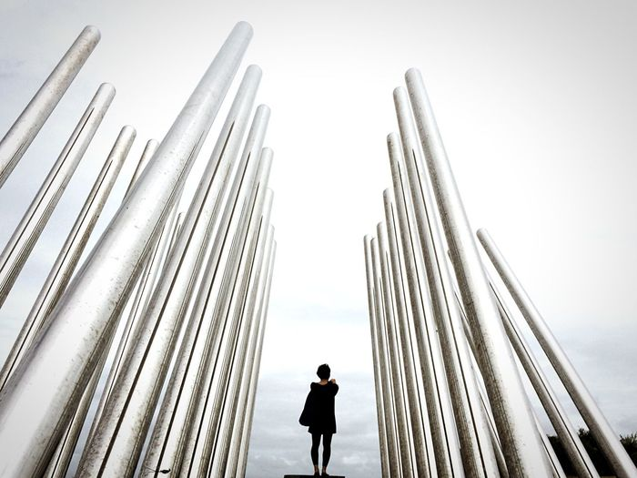 Rear view of woman standing amidst metal poles against sky