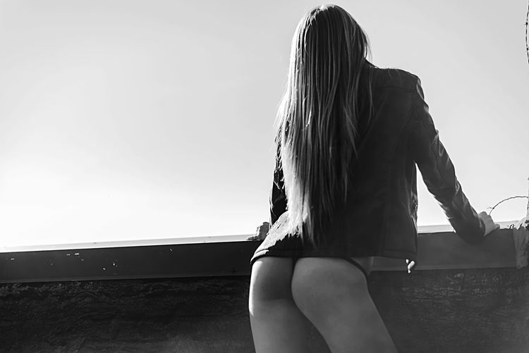 Rear view of woman sitting against sky