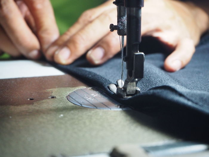 Cropped hands sewing fabric