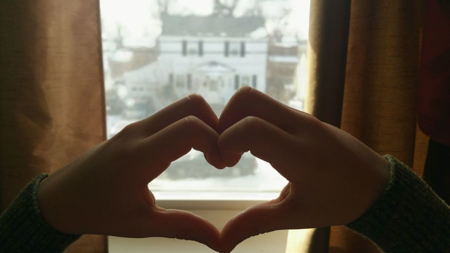 Cropped hands making heart shape against window