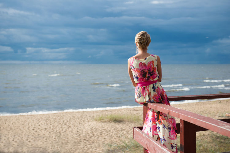 Rear view of woman sitting on railing against beach