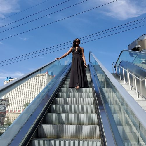 Low angle view of woman standing on escalator against sky