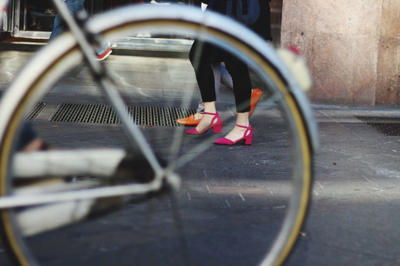 Close-Up Of Bicycle Wheel With Low Section Of Women In Background