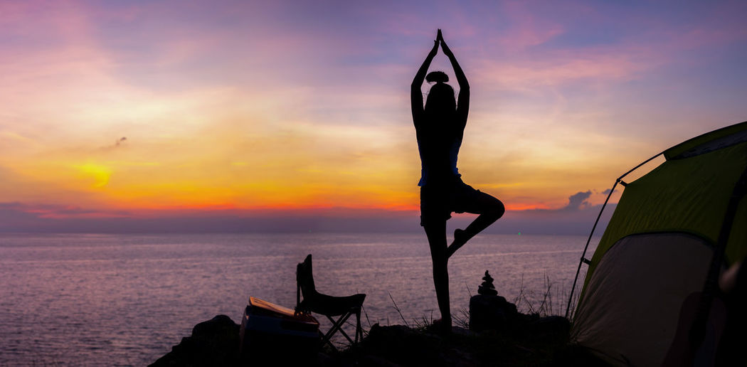 Young woman practicing yoga in the nature.female happiness. Landscape background Yoga Yoga Pose Yogagirl Sunset Silhouette Sea Beauty In Nature Arms Raised Lifestyles Sport Fit Sexygirl Health Travel Tourist Relaxing Rest Homeopathic Medicine Homeopathic Exercising Happiness Camping Backpack Hiking Outdoors
