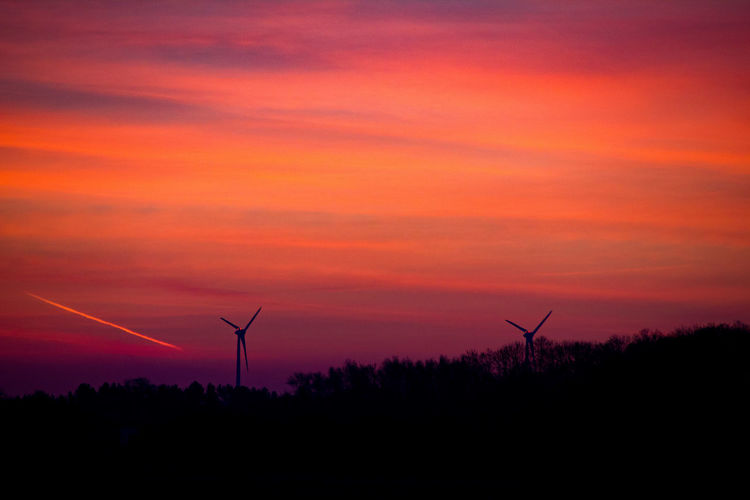 Silhouette windmills on field against orange sky