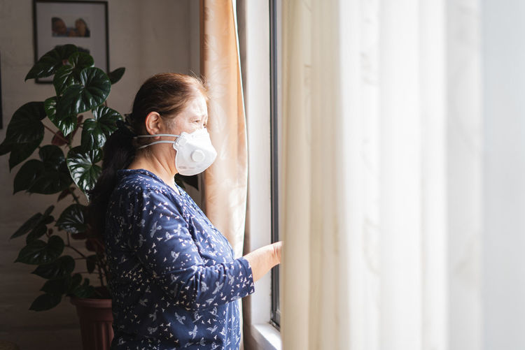 Woman wearing mask looking through window at home