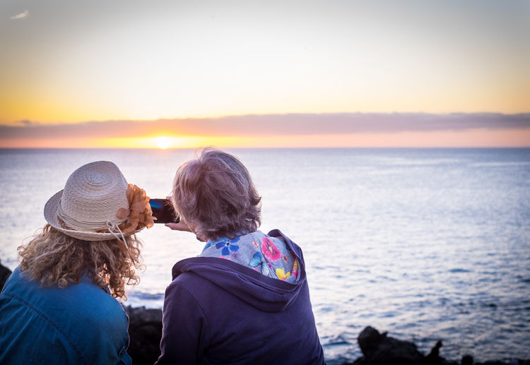 Rear view of friends looking at sea against sky during sunset