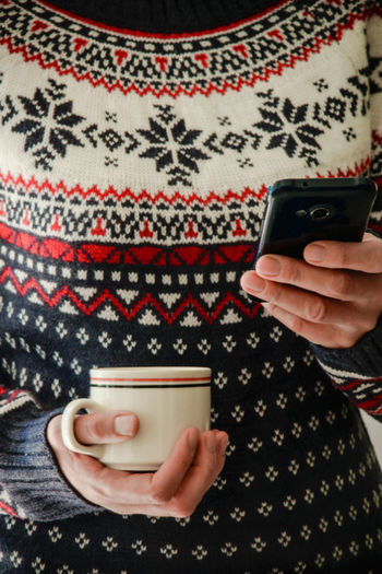 Close-Up Of Woman With Coffee Cup Using Mobile Phone