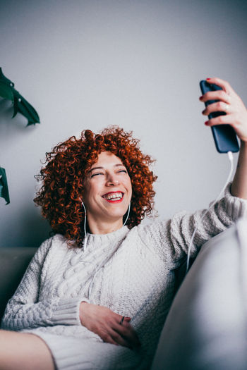 Smiling woman taking selfie while sitting on sofa at home