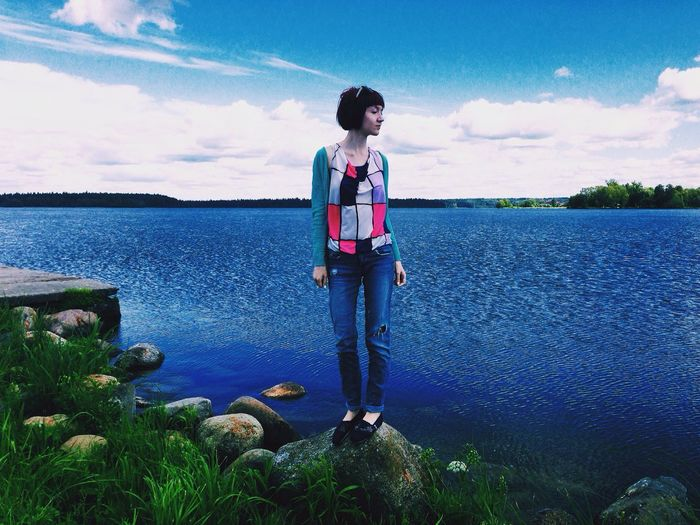 Full length of girl standing on rock against lake and cloudy sky