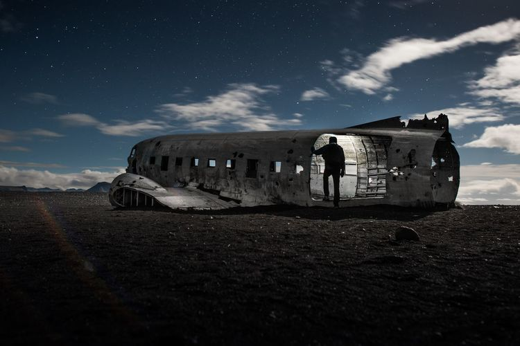 Man Standing In Abandoned Airplane Against Sky